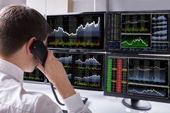 Close-up Of Stock Broker Talking On Telephone. Stock Broker Talking On Telephone In Front Of Multiple Computer Screen Showing Graphs Royalty Free Stock Photography