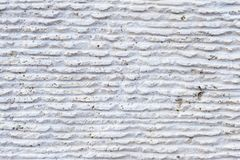 Close-up of stone surface with traces of processing. Parallel lines on the stone left by the cutting tool. Abstract. Textured background of white porous stone stock photo
