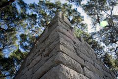 Close up of a stone wall corner, with trees an sky stock photography