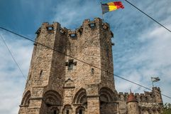 Close-up of stone watch-tower and flag in the Gravensteen Castle at Ghent. stock photos