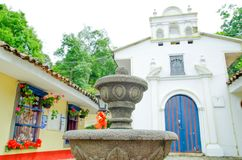 Close up of stoned fountain without water with white small cathedral in Popayan town in a gorgeous sunny day, visited. For many tourists for be a quite place in Stock Image