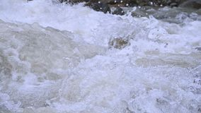 Close-up stones and spray of a stormy mountain river in slow motion with tracking wiring. The concept of global warming