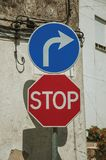 Close-up of STOP and TURN RIGHT AHEAD road signs. In front of worn plaster wall, in a sunny day at Gouveia. A nice country town with gardens and captivating royalty free stock photography