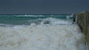 Close-up stormachtige golven die vuil overzees schuim langs kust bewegen stock video