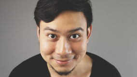 Close up straight face with smile. An asian man with black t-shirt stock photo