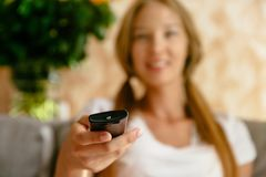 Tv remote control in woman hand royalty free stock image