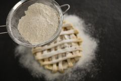 Close up of strainer over pie Stock Photo