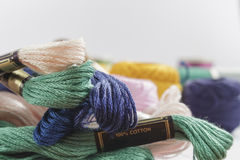 Close-up of stranded cotton thread light pink, green and dark blue. Behind, out of focus, it can be seen several bobbins for sewing machines. On white Stock Photography