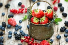 An antic pail on rustic table full with berries - strawberries, currants, blueberries. Close-up of strawberries in an antic pail on rustic table full with royalty free stock image