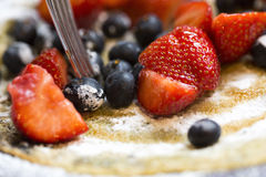 Close up of strawberries and blueberries on a pancake covered in icing sugar and maple syrup Stock Images