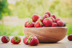 Close-up of strawberries in vintage wooden bowl on wooden table Stock Photos
