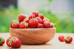 Close-up of strawberries in vintage wooden bowl on wooden table Stock Photo