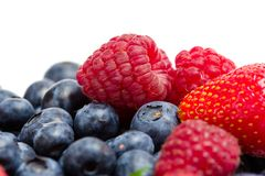 Close up of strawberry, bilberry and raspberry. Close up of heap of strawberry, bilberry and raspberry, isolated on white. Concept of healthy eating and dieting Royalty Free Stock Photo