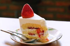 A strawberry shortcake topped with a large fresh strawberry placed in white plate and on wooden table with cafe environment. Close up a strawberry shortcake Stock Photography