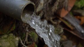 Close up stream of drainage rainwater flows from a plastic pipe in nature.