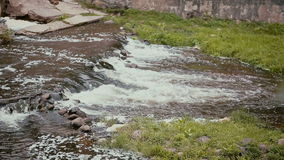 A close up of a stream of water coming down from a small waterfall with loud noise stock video footage