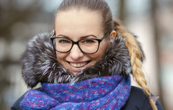 Close up street portrait of young smiling blonde woman in glasses wearing blue knitted scarf posing on street at cold season. stock photos