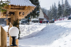 Close up on streetlight in a snow-covered skiing town. On a sunny winter day Stock Photography