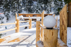 Close up on streetlight on wooden bridge in a snow-covered skiin. G town on a sunny winter day Stock Photos