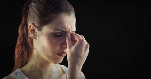 Close up of stressed woman against black background with grunge overlay Royalty Free Stock Photography