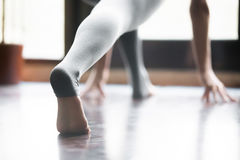 Close up of stretched leg, yoga pants with heel cover. Close up of female stretched barefoot leg in sportswear, grey yoga pants with heel cover for practicing royalty free stock image
