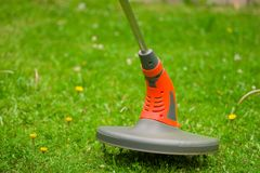 Close up of string lawn trimmer mower cutting grass, over a grass background.  Stock Photography
