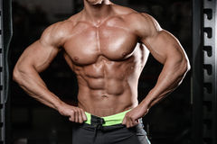 Close up strong abs guy showing in the gym muscles stock photo