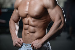 Close up strong abs guy showing in the gym muscles stock images