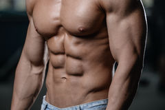 Close up strong abs guy showing in the gym muscles stock photography
