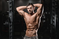 Close up strong abs guy showing in the gym muscles. Strong athletic man fitness model torso showing six pack abs close up strong abs guy showing in the gym Royalty Free Stock Image