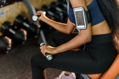 Close-up strong hands of sexy fitness african american woman working out with dumbbells at the gym and listens music in Royalty Free Stock Photo