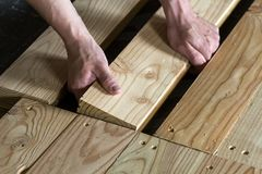Close up of strong muscular hands of professional carpenter inst. Alling natural wooden new planks on wooden frame floor Reconstruction, improvement, renovation Stock Images