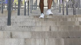 Close-up of strong muscular legs running down concrete stairway in slow-motion. Stock footage stock video