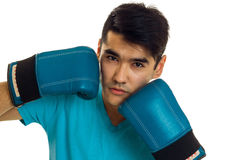 Close up of strong young brunette man in blue gloves practicing boxing and looking at the camera isolated on white.  Stock Photo
