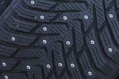 Close-up of a studded tire with spikes for winter driving. Close-up of a studded tire profile with spikes for winter driving on ice and snow royalty free stock photos