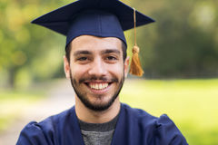 Close up of student or bachelor in mortar board. Education, graduation and people concept - close up of happy student in mortar boards and bachelor gown outdoors Royalty Free Stock Images