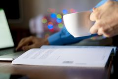 Close up student doing homework on the table at home, using naptop and book, drink tea f royalty free stock photo