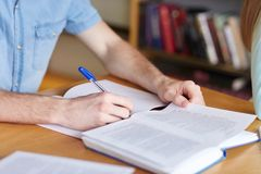 Close up of student hands writing to notebook. People, learning, education and school concept - close up of student boy hands with book or textbook writing to Royalty Free Stock Images