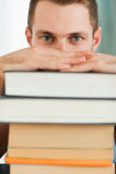 Close up of student hiding behind a pile of books Royalty Free Stock Photos
