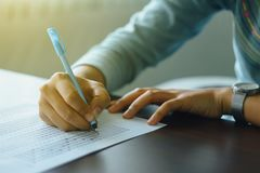 Close up of student`s hand holds a pen write on answer sheet. Student answers multiple choice questions on wooden table in examin Royalty Free Stock Photo