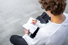 Close up of student on steps of modern building and writing text in notepad. royalty free stock image