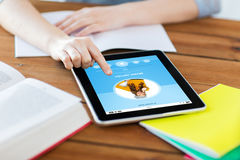 Close up of student with tablet pc and notebook. Multimedia, education, technology and internet concept - close up of student women with music player on tablet Stock Image
