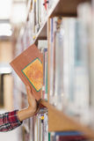 Close up of student taking book out of shelf Royalty Free Stock Images