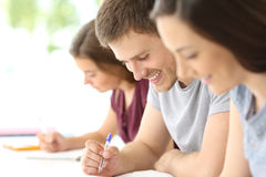 Close up of a student taking notes. Close up of a happy student taking notes in a classroom Stock Photos