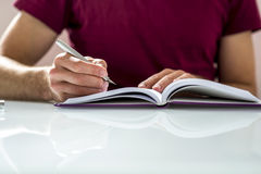 Close up of a student Writing Notes or Homework on a Clean Noteb. Ook on Top of White Table Stock Images