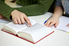 Close up of students hands with book or textbook. Education, people and school concept - close up of students hands reading textbook or book at school Stock Images