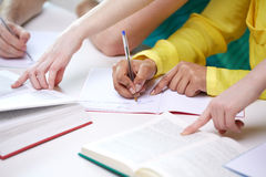 Close up of students hands writing to notebooks Stock Photo