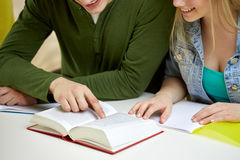 Close up of students reading book or textbook. Education, people and school concept - close up of happy students reading textbook or book at school Royalty Free Stock Images