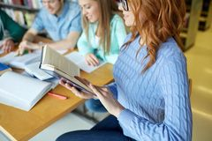 Close up of students reading books at school. People, knowledge, education and school concept - close up of happy students reading books and preparing to exam in Royalty Free Stock Image