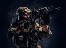 Close-up studio photo against a dark wall. The elite unit, special forces soldier in camouflage uniform holding an. Close-up studio photo against a dark textured stock photos